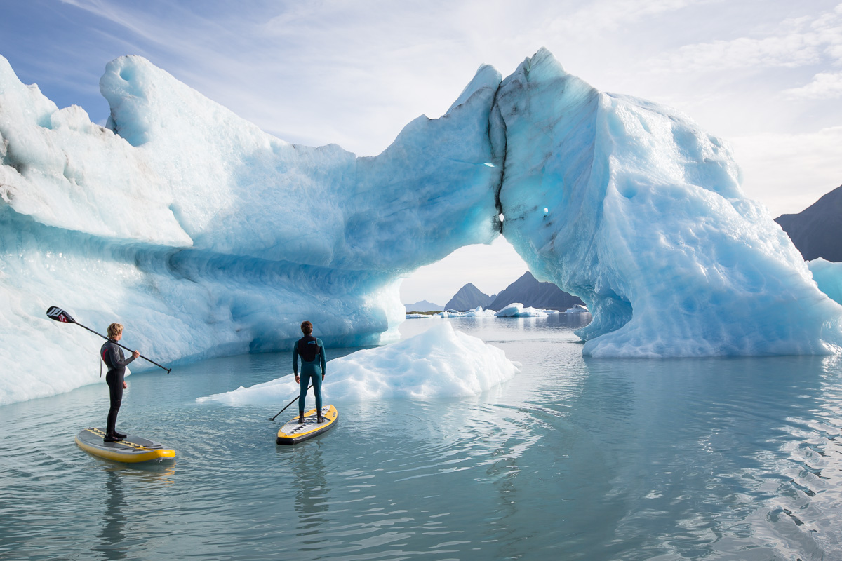 Kevin Langeree and Kai Lenny stand up paddle around a large iceberg with an arch formed in it in a glacier lake in Southcentral Alaska.
